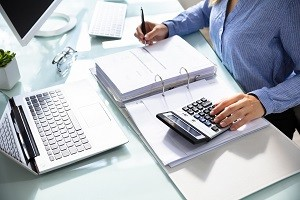 Businesswoman's Hand Calculating Bill In Office